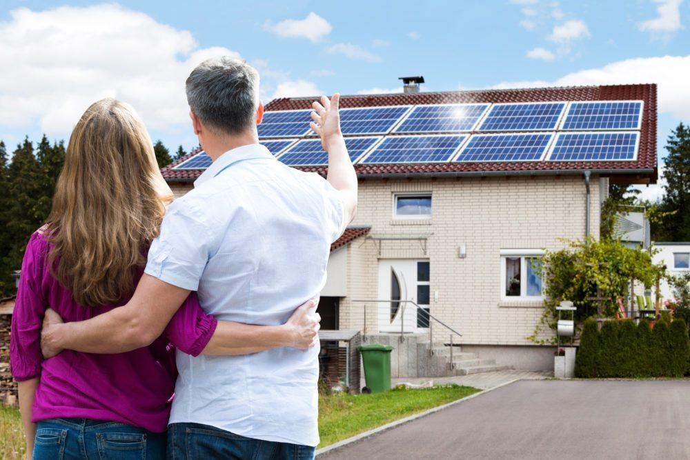 Koppel bekijkt zonnepaneleninstallatie op dak. Ga met Luminus voor een optimale opbrengst van zonnepanelen.